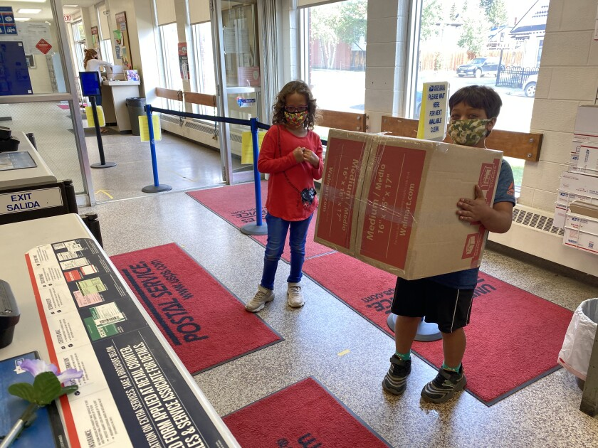 Young customers wait to mail a package at the Leadville, Colo., post office.