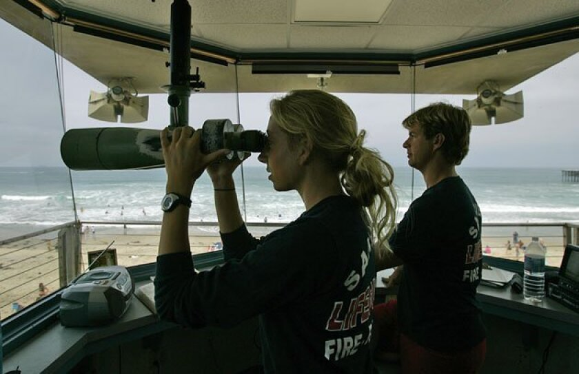 San Diego lifeguards Katelyn Schlactus (left) and Sean Dale looked out over Pacific Beach from the main lifeguard station at the foot of Grand Avenue.  (K.C. Alfred / U-T)