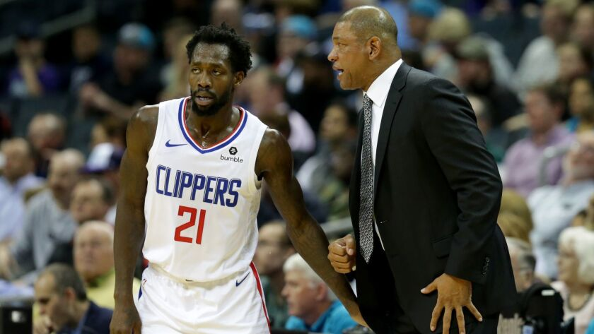 Clippers guard Patrick Beverley speaks with coach Doc Rivers during a game against the Charlotte Hornets on Feb. 5.