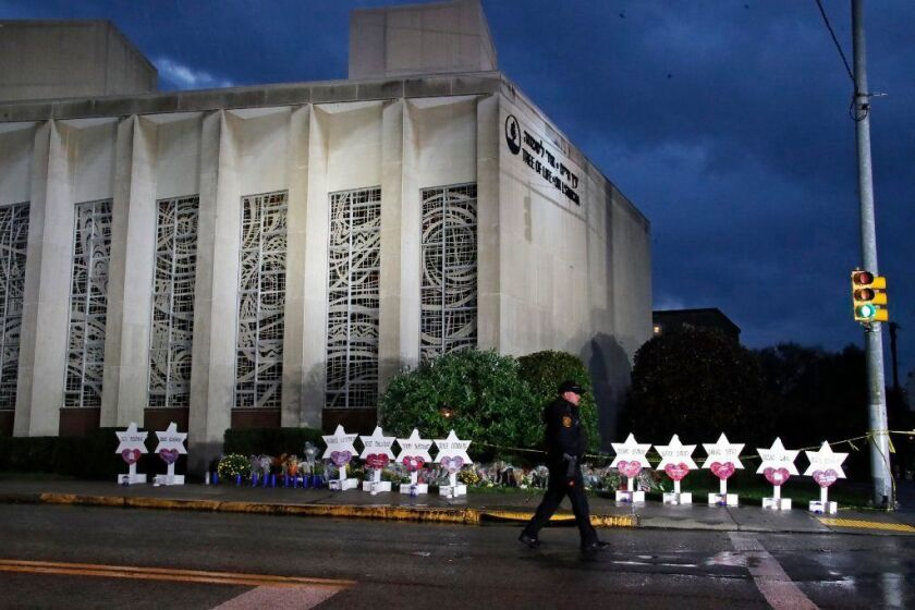 A Pittsburgh police officer walks past the Tree of Life Synagogue and a memorial of flowers and stars in Pittsburgh in remembrance of those killed and injured when a shooter opened fire during services Saturday.