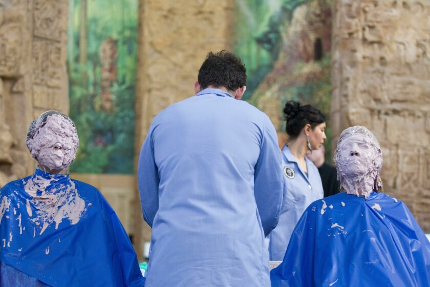 Dianne Berg (left) and Jan Wallden wait for a facial coating to dry as Jerry Blackman prepares plaster Sunday at the Museum of Man.