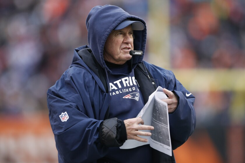 New England Patriots coach Bill Belichick stands on the sideline.