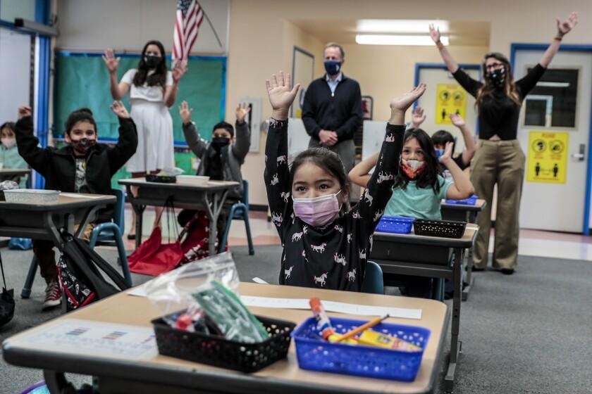 Kindergarten children in masks sitting at desks raise their hands for a photo