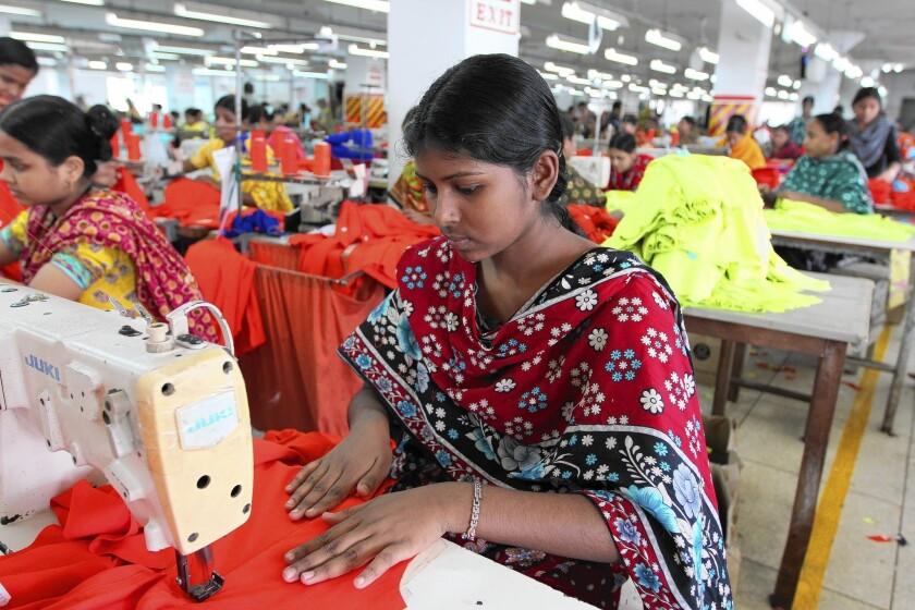 A garment factory worker toils in Dhaka, Bangladesh