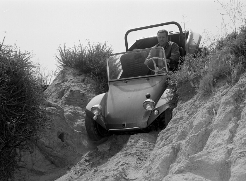 Bruce Meyers in his Manx dune buggy going down a sand dune.