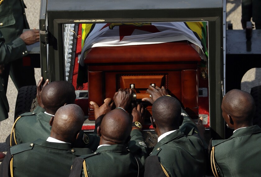 The casket of former president Robert Mugabe is loaded by military officers into a vehicle as it departs after a state funeral at the National Sports Stadium in Harare, Zimbabwe, Saturday, Sept. 14, 2019. African heads of state and envoys gathered to attend a state funeral for Zimbabwe's founding president, Robert Mugabe, whose burial has been delayed for at least a month until a special mausoleum can be built for his remains. (AP Photo/Themba Hadebe)