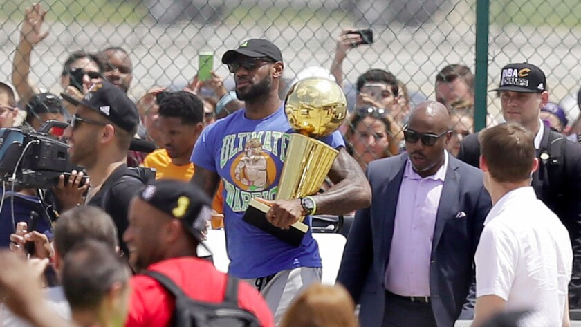 Cleveland Cavaliers' LeBron James carries the NBA Championship trophy after arriving in Cleveland.