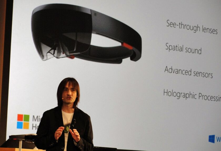 Microsoft executive Alex Kipman speaks at the firm's Redmond, Wash., campus on Wednesday as he introduces HoloLens headgear that overlays 3-D objects on the real world.