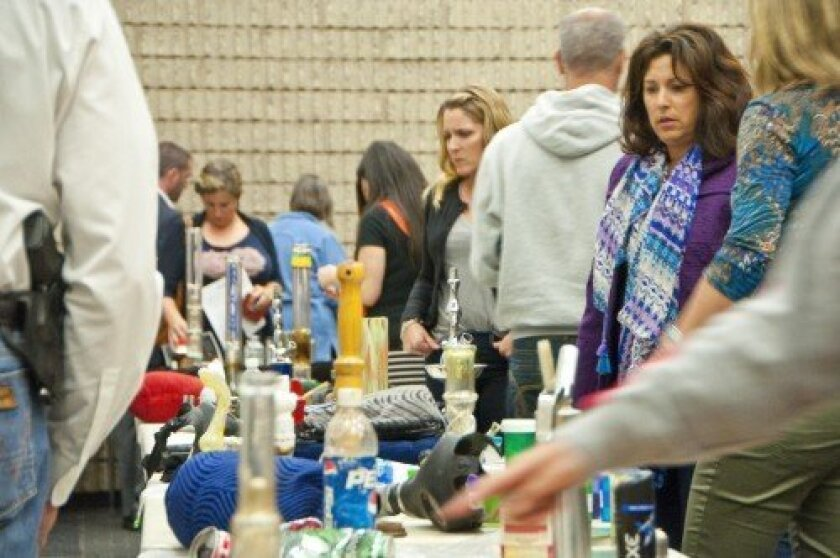 Parents on Nov. 8 observe hundreds of confiscated items such as drugs, paraphernalia and weapons at a special program on the topic of youth subcultures and substance abuse.