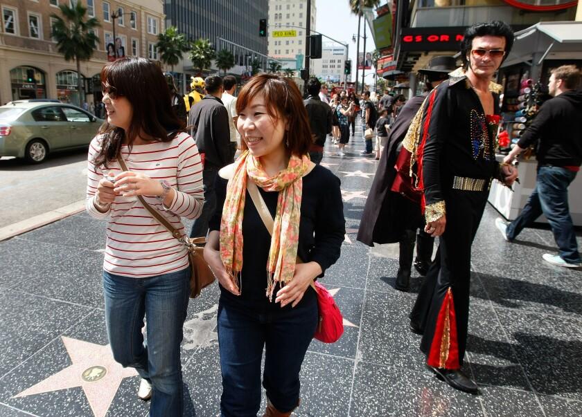 Tourists Miwako Tsugawa, left, and Yuka Watanabe, from Nagoya, Japan, check out the sights while walking along Hollywood Boulevard.