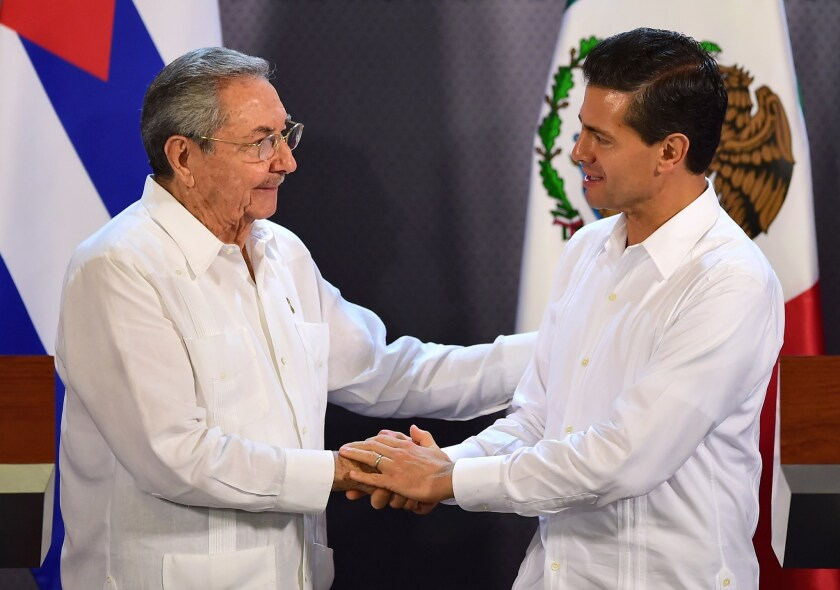 Mexican President Enrique Peña Nieto, right, and Cuban President Raul Castro shake hands during a news conference at the government palace in Merida, Mexico, on Nov. 6.