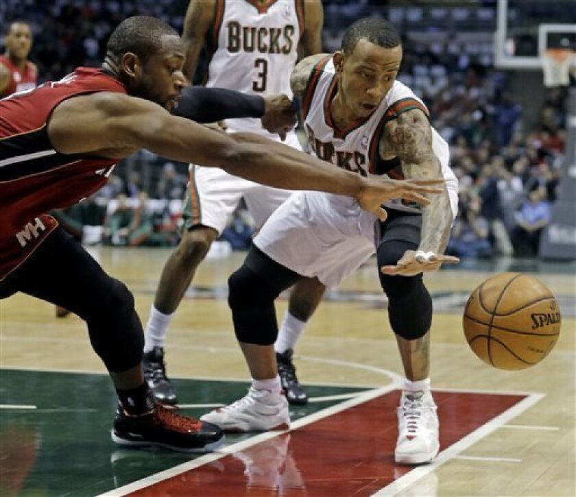 Milwaukee Bucks' Monta Ellis, right, and Miami Heat's Dwyane Wade battle for a loose ball during the first half of Game 3 in their first-round NBA basketball playoff series on Thursday, April 25, 2013, in Milwaukee. (AP Photo/Morry Gash)