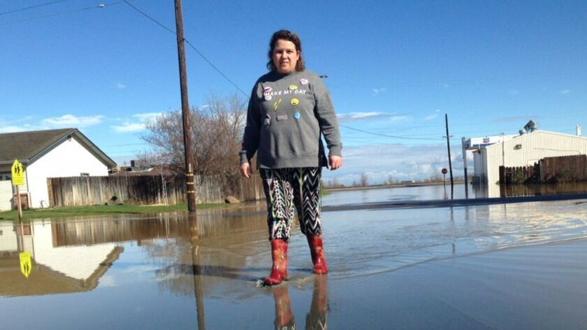 Blanca Velasquez was among many searching for dry ground Saturday in the flooded town of Maxwell, south of Oroville.