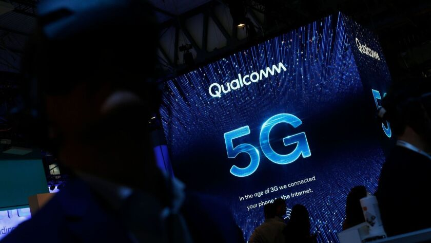 People visit the Qualcomm stand at the Mobile World Congress in Barcelona in February.