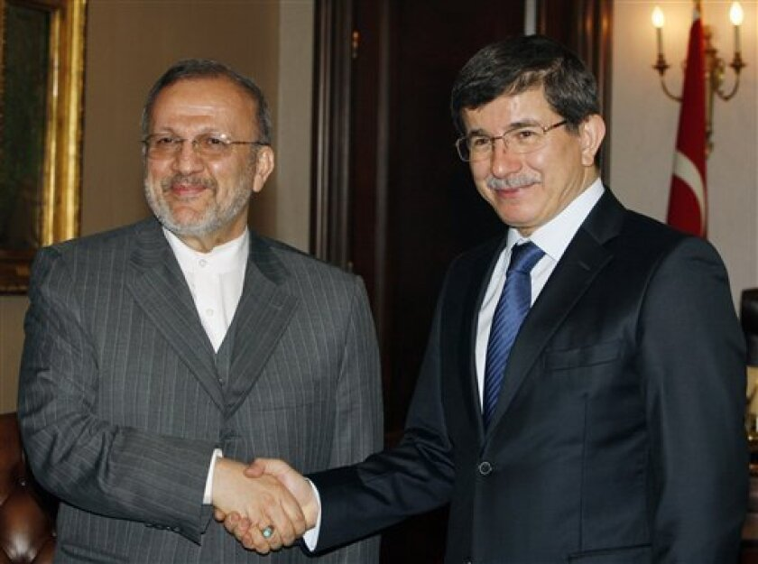 Turkish Foreign Minister Ahmet Davutoglu, right, and his Iranian counterpart Manouchehr Mottaki pose for cameras before their talks in Ankara, Turkey, Wednesday, Feb. 3, 2010. Mottaki is in Turkey for a two-day visit.(AP Photo/Burhan Ozbilicil)