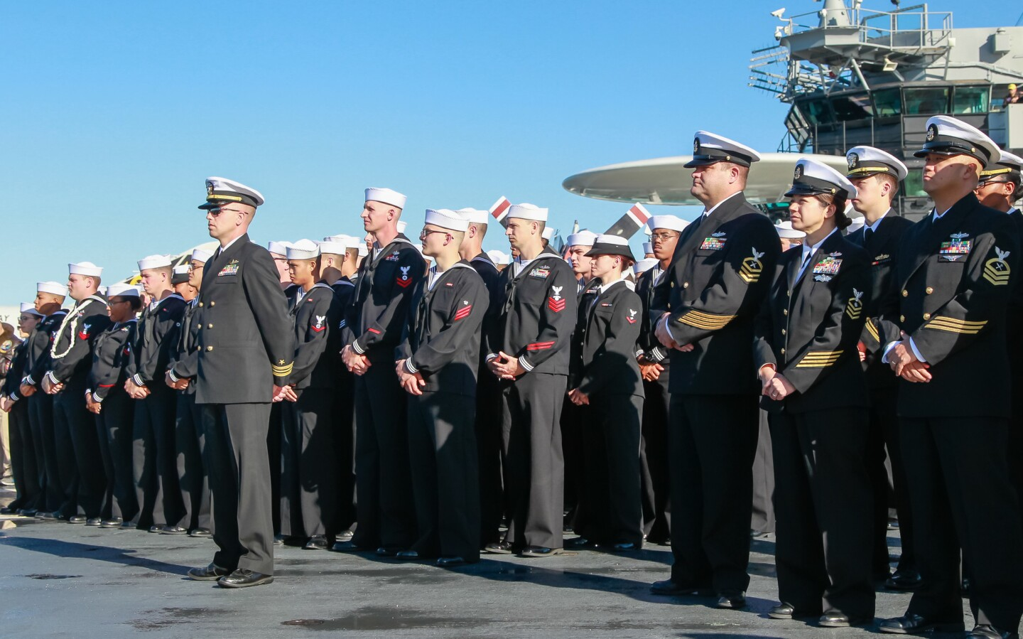 Sailors from the ship called, USS Pearl Harbor stand at attention.