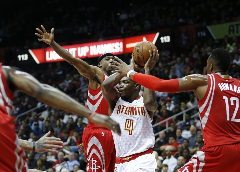 Atlanta Hawks forward Paul Millsap (4) works against Houston Rockets guard Jason Terry (31) and center Dwight Howard (12) in the first half of an NBA basketball game Saturday, March 19, 2016, in Atlanta. (AP Photo/John Bazemore)
