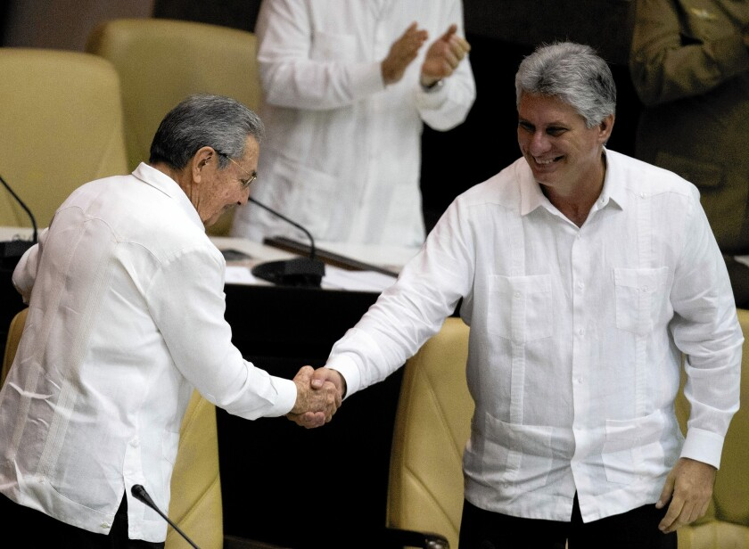 Miguel Diaz-Canel, right, shakes hands with Cuban President Raul Castro. Castro's appointment of Diaz-Canel as first vice president in 2013 set him up as heir apparent of Cuba.
