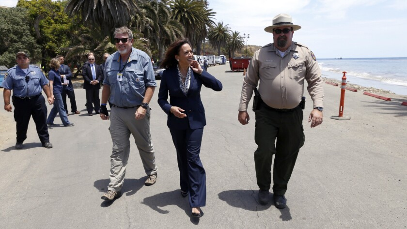 State Atty. Gen. and U.S. Senate candidate Kamala Harris, center, is briefed by Tyson Butzke, right, a superintendent with California State Parks, and Tom Cullen, left, of the Department of Fish and Wildlife, at Refugio State Beach on Thursday.
