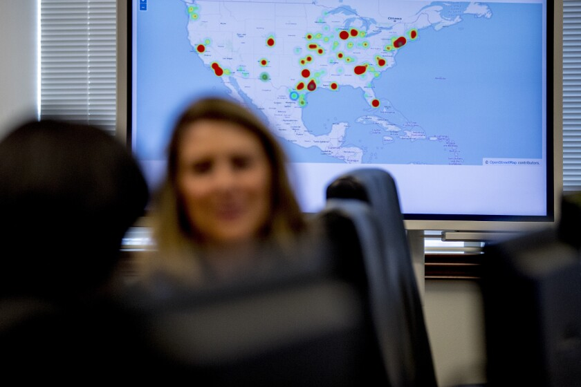 """A monitor displaying arrests made across the country as part of """"Project Python"""" is visible behind Drug Enforcement Administration agents and intelligence analysts gathering information from field operations across the country at their command center in Chantilly, Va., Wednesday, March 11, 2020. (AP Photo/Andrew Harnik)"""