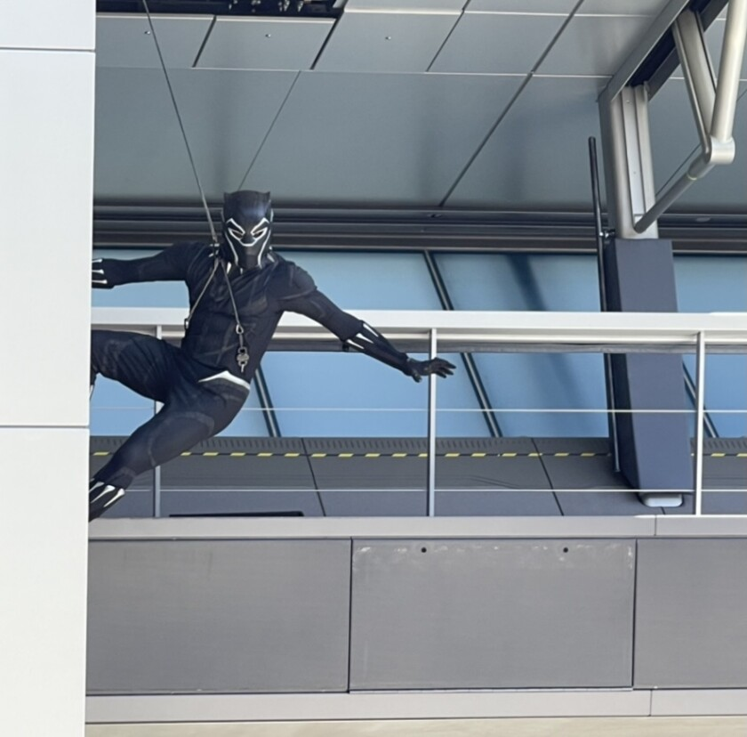 Black Panther is attached to a wire in front of a building.