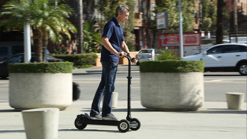 Phil LaBonty demonstrates his company's three-wheeled CycleBoard at the L.A. Auto Show.