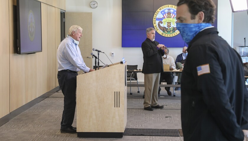 County Supervisor Greg Cox (left) speaks during a Friday press briefing announcing new orders directed at stopping the spread of the coronavirus. Supervisor Nathan Fletcher (right) also spoke at the press briefing, held the day after county officials advised all people to wear facial coverings when leaving their homes.