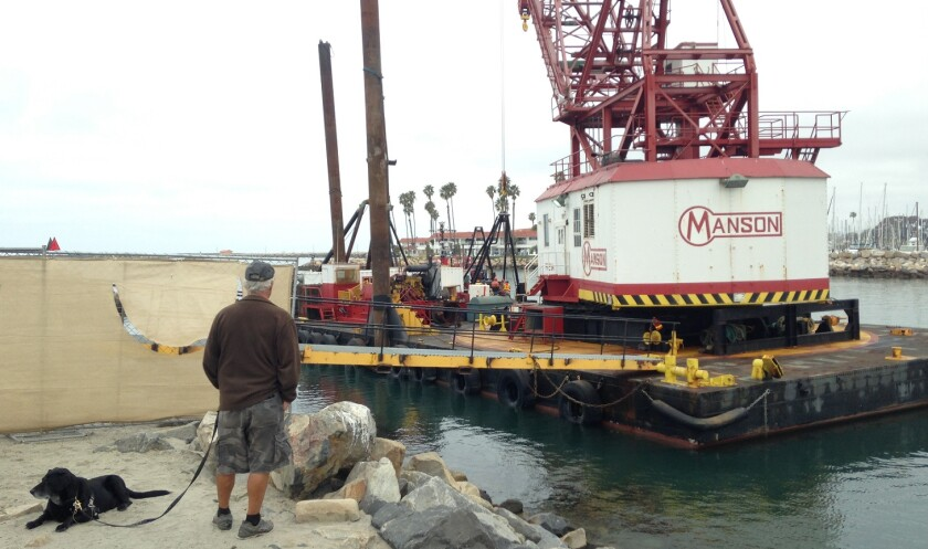 A man watches Manson Construction workers prepare a barge to begin dredging the Oceanside Harbor last Friday.
