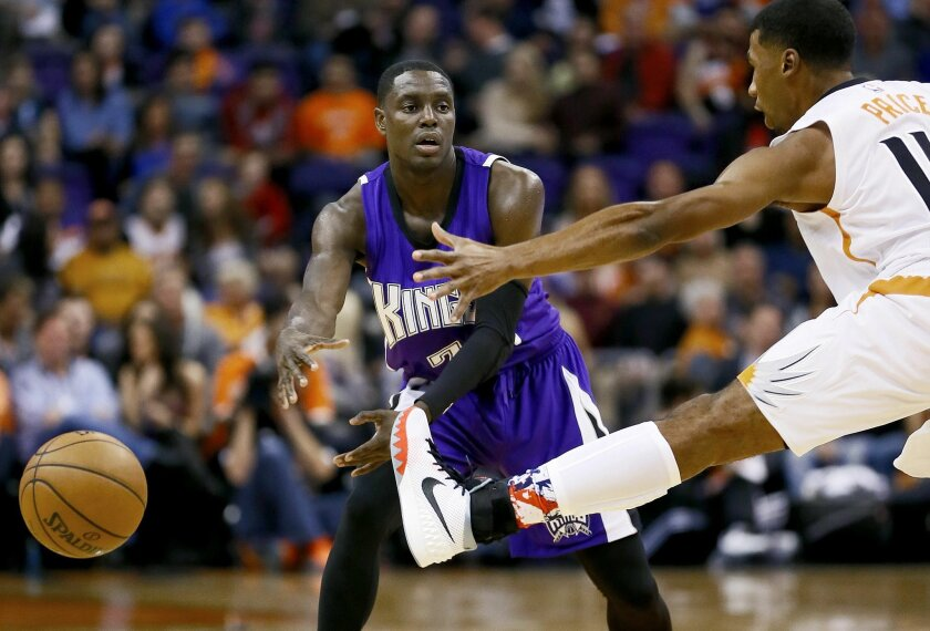 Sacramento Kings' Darren Collison passes under Phoenix Suns' Ronnie Price during the first half of an NBA basketball game, Wednesday, Nov. 4, 2015, in Phoenix. (AP Photo/Matt York)