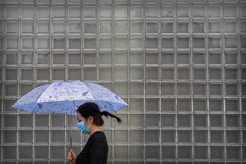Una mujer, con mascarilla para protegerse del coronavirus pasa por delante de un centro de comercial en un día lluvioso en Beijing, el 23 de septiembre de 2020. (AP Foto/Mark Schiefelbein)
