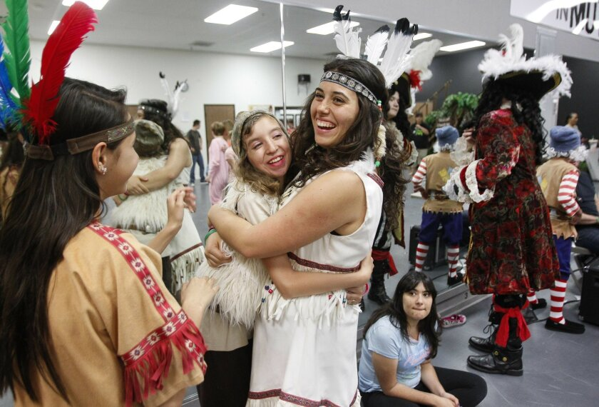 "Melanie Hambrick (right), who plays Tiger Lily, hugs fellow actor Evelyn Woodard during a rehearsal for Arms Wide Open's production of ""Peter Pan Jr."""