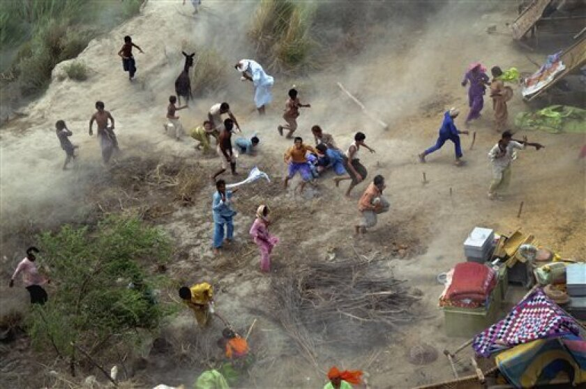 Pakistani villagers chase to relief supplies dropped from an army helicopter in a heavy flood-hit area of Mithan Kot, in central Pakistan, Monday, Aug. 9, 2010. The government has struggled to cope with the scale of the disaster, which has killed at least 1,500 people, prompting the international c