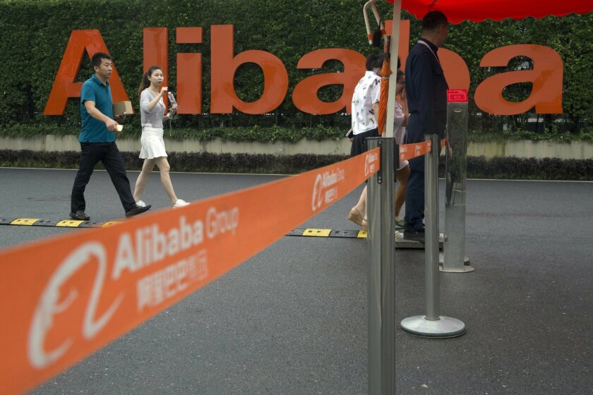 Staffers past security guards near a company logo at the Alibaba Group headquarters in Hangzhou, in eastern China's Zhejiang province on Friday, May 27, 2016. Alibaba's relationship with an anti-counterfeiting lobby coalition known as the International Anti-Counterfeiting Coalition is a tale of how