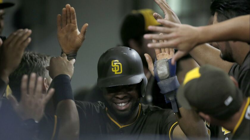 San Diego Padres' Manuel Margot, center, gets congratulations from teammates after scoring on an Aus