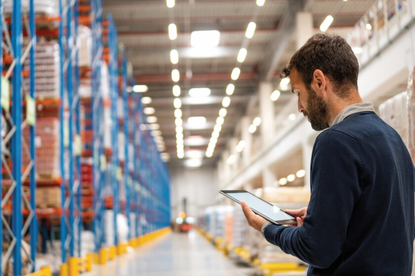 man in a warehouse looking at data