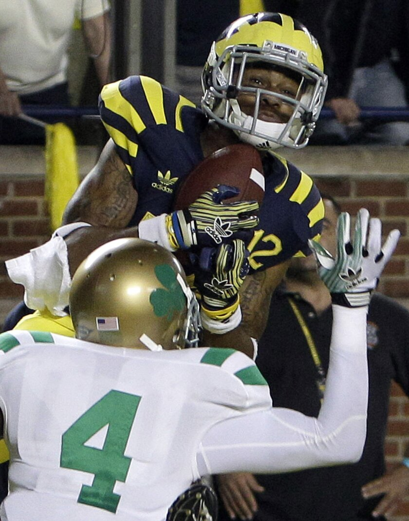 FILE - In this Sept. 10, 2013, file photo, Michigan wide receiver Roy Roundtree catches the game-winning touchdown pass over Notre Dame cornerback Gary Gray (4) during the closing seconds of the fourth quarter of an NCAA college football game in Ann Arbor, Mich. Michigan won 35-31. (AP Photo/Carlos Osorio, File)