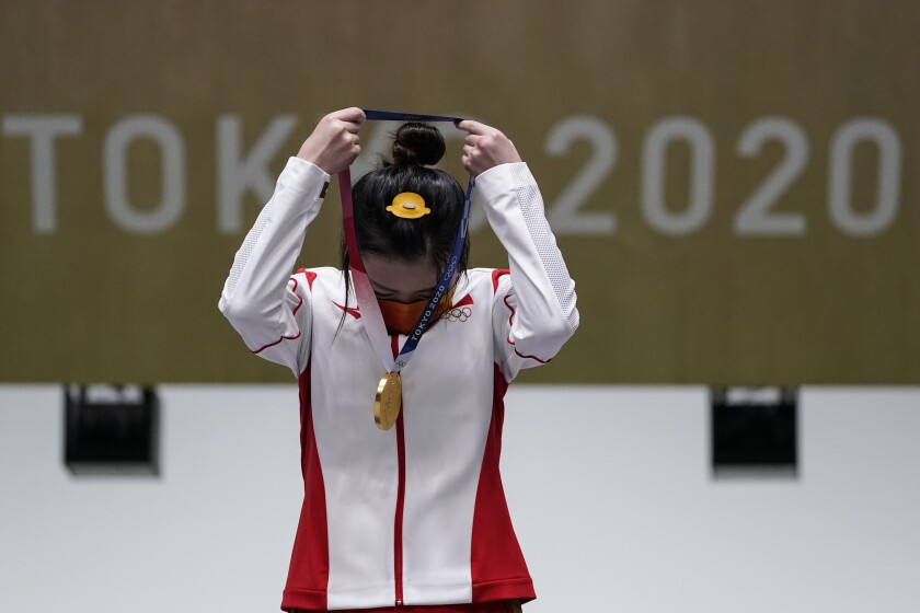 Yang Qian, of China, puts her gold medal on after winning the women's 10-meter air rifle at the Asaka Shooting Range in the 2020 Summer Olympics, Saturday, July 24, 2021, in Tokyo, Japan. (AP Photo/Alex Brandon)