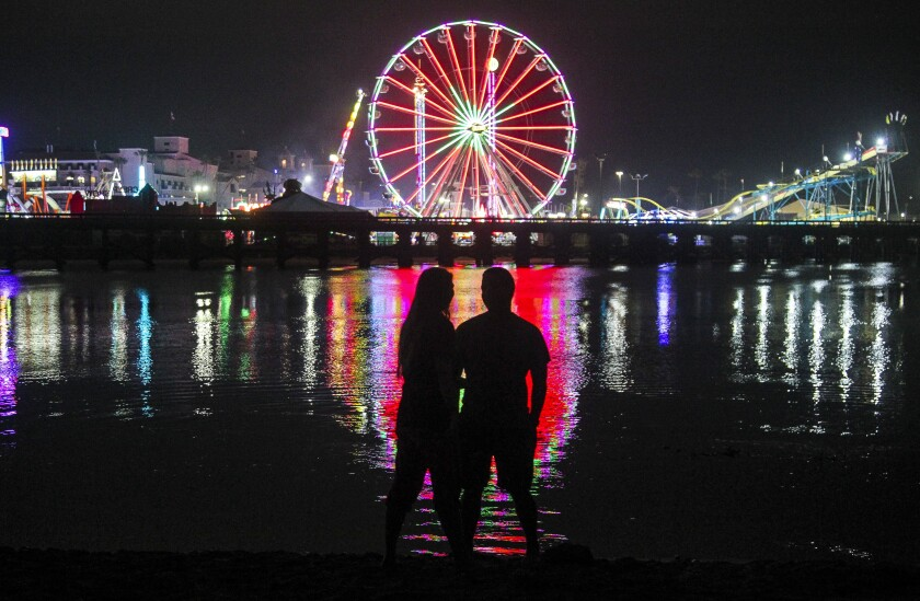 A couple  stand at the edge of the San Dieguito River as they watch the lights of the San Diego County Fair.