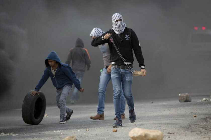 Palestinian protesters prepare to throw stones towards Israeli troops during clashes outside Ofer military prison near the West Bank city of Ramallah, Tuesday, Nov. 3, 2015. (AP Photo/Majdi Mohammed)