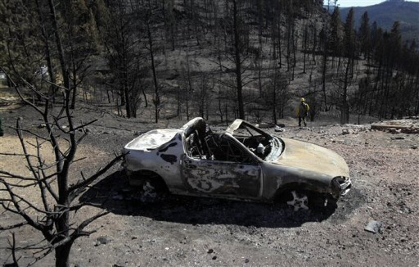 A car destroyed by the Fourmile Canyon fire is seen in Sunshine Canyon, west of Boulder, Colo., Saturday, Sept. 11, 2010. Fire managers are confident they've stopped a wildfire burning in the Colorado foothills from spreading, but people who live in the blaze's path still didn't know Saturday when they would be able to return to their homes or what remains of them. (AP Photo/Jae C. Hong)