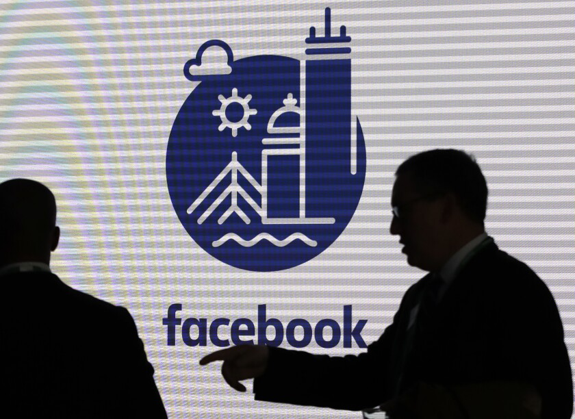 FILE - In this Jan. 9, 2019, file photo, media and guests mingle before a tour of Facebook's new 130,000-square-foot offices, which occupy the top three floors of a 10-story Cambridge, Mass. building. Facebook and Twitter's announcements Thursday, March 12, 2020, that they have removed dozens of accounts and pages from their services show that Russia's efforts to interfere in the U.S. presidential election are getting more sophisticated and harder to detect. (AP Photo/Elise Amendola, File)