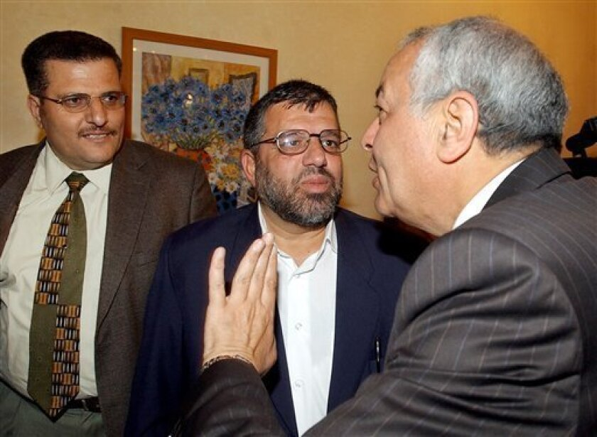 FILE - In this Sunday, May 29, 2005 file photo, Palestinian militant group Hamas for the West Bank Hassan Yousef, center, stands with Egyptian mediator Mustafa Buhairi, right, and an unidentifed Hamas representative, during meetings in the West Bank city of Ramallah. The son of one of Hamas' founders Sheik Hassan Yousef served as a top informant for Israel for over a decade, providing top-secret intelligence that helped prevent dozens of suicide bombings and other attacks against Israelis, the Israeli daily Haaretz reported Wednesday 24, 2010. The younger Yousef converted to Christianity and moved to the California in 2007. (AP Photo/Nasser Shiyoukhi, File)
