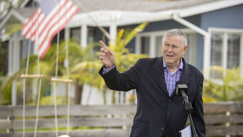Rep. Dana Rohrabacher points to a commercial aircraft that could be heard leaving nearby John Wayne Airport during a news conference Monday outside his Costa Mesa home.
