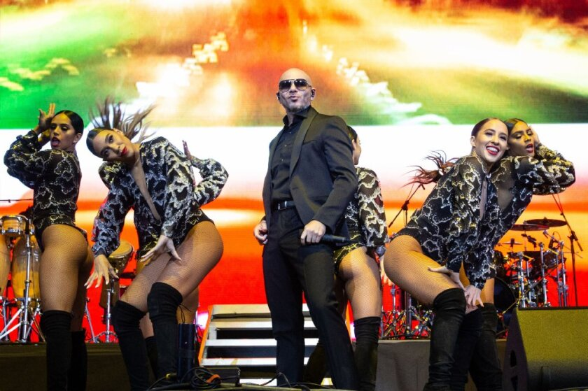 A 2016 Grammy Award-winner, Pitbull (center) raps in English and Spanish.