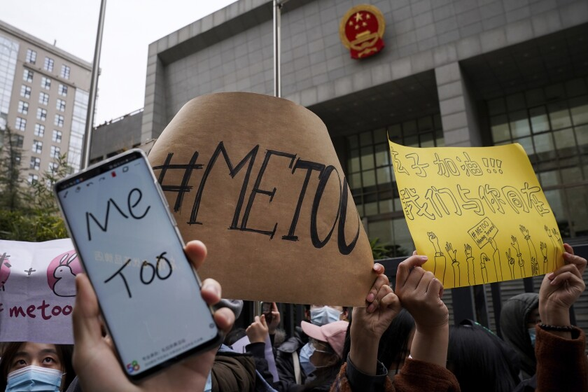 Supporters hold banners as they wait for of Zhou Xiaoxuan outside at a courthouse where Zhou is appearing in a sexual harassment case in Beijing on Wednesday, Dec. 2, 2020. In a blow to the MeToo movement in China, a court in Zhejiang province found a young man and woman guilty of defamation against a prominent Chinese journalist on Tuesday, Jan. 5, 2021 for publishing an alleged account of sexual harassment. (AP Photo/Andy Wong)