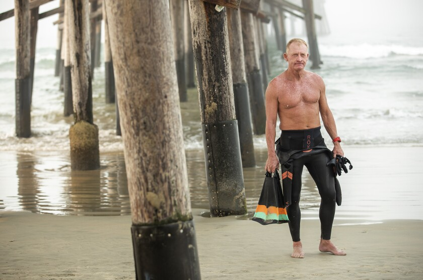 Kenneth Mullinix, who survived a stroke in 2015, prepares for a swim in the ocean near the Newport Beach Pier.