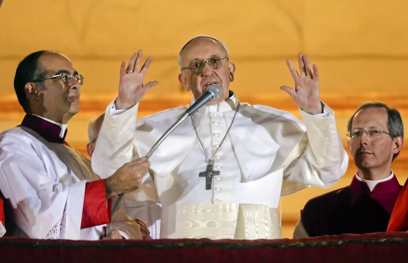 Pope Francis waves from the central balcony of St. Peter's Basilica at the Vatican, the day of his election.