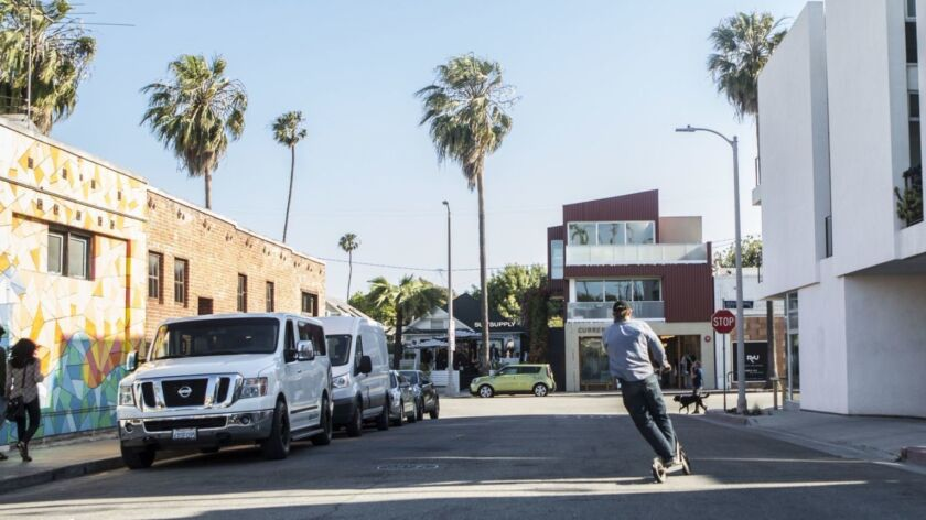 A man rides a motorized Bird scooter toward Abbott Kinney Boulevard in Venice. Los Angeles city officials are considering regulations on where the scooters can be parked.