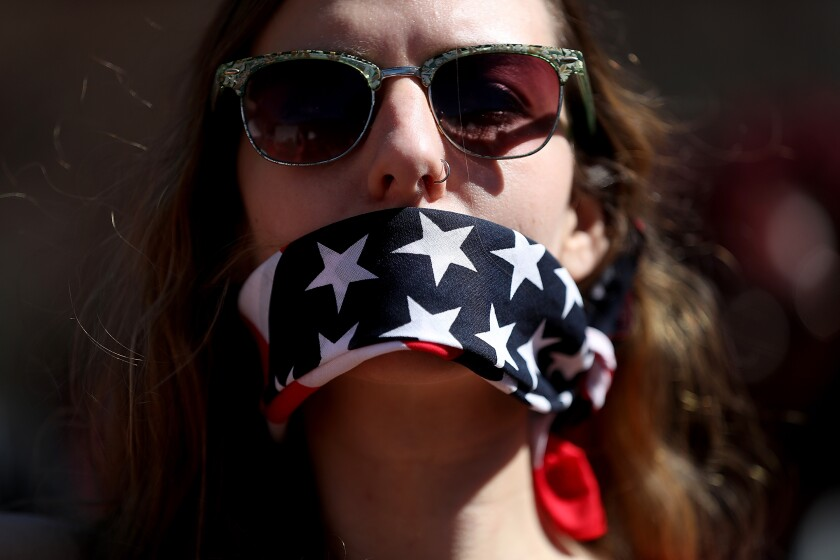 A protester wears a banda,na over her mouth during a rally to support women's health programs.