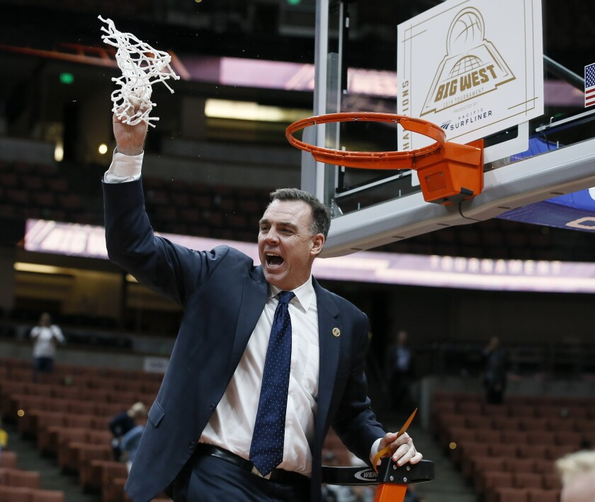 UC Irvine coach Russell Turner celebrates after cutting down the net as his team beat Cal State Fullerton 94-64 for the Big West Conference Tournament title at Honda Center on March 16.
